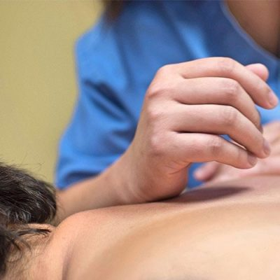 massage therapist helping patient with neck pain relief